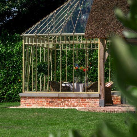 Smeedijzeren orangerie in combinatie met eiken constructie met rieten dak