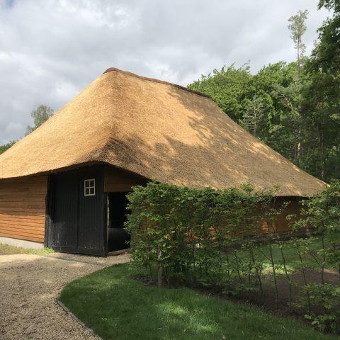 Houten bijgbouw met rieten dakbedekking